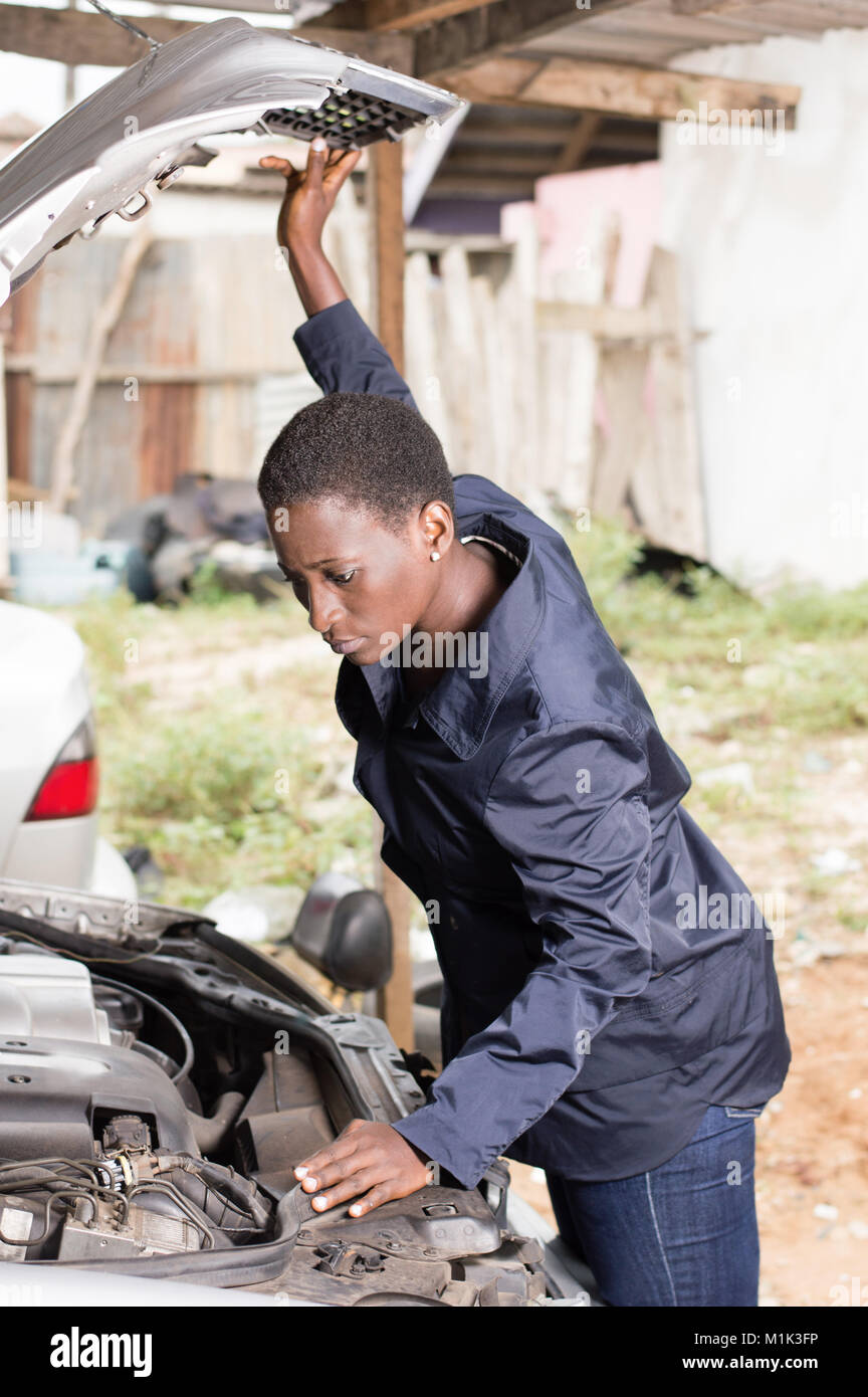 Mechanic looks into the engine of a car parked in her   workshop. - Stock Image