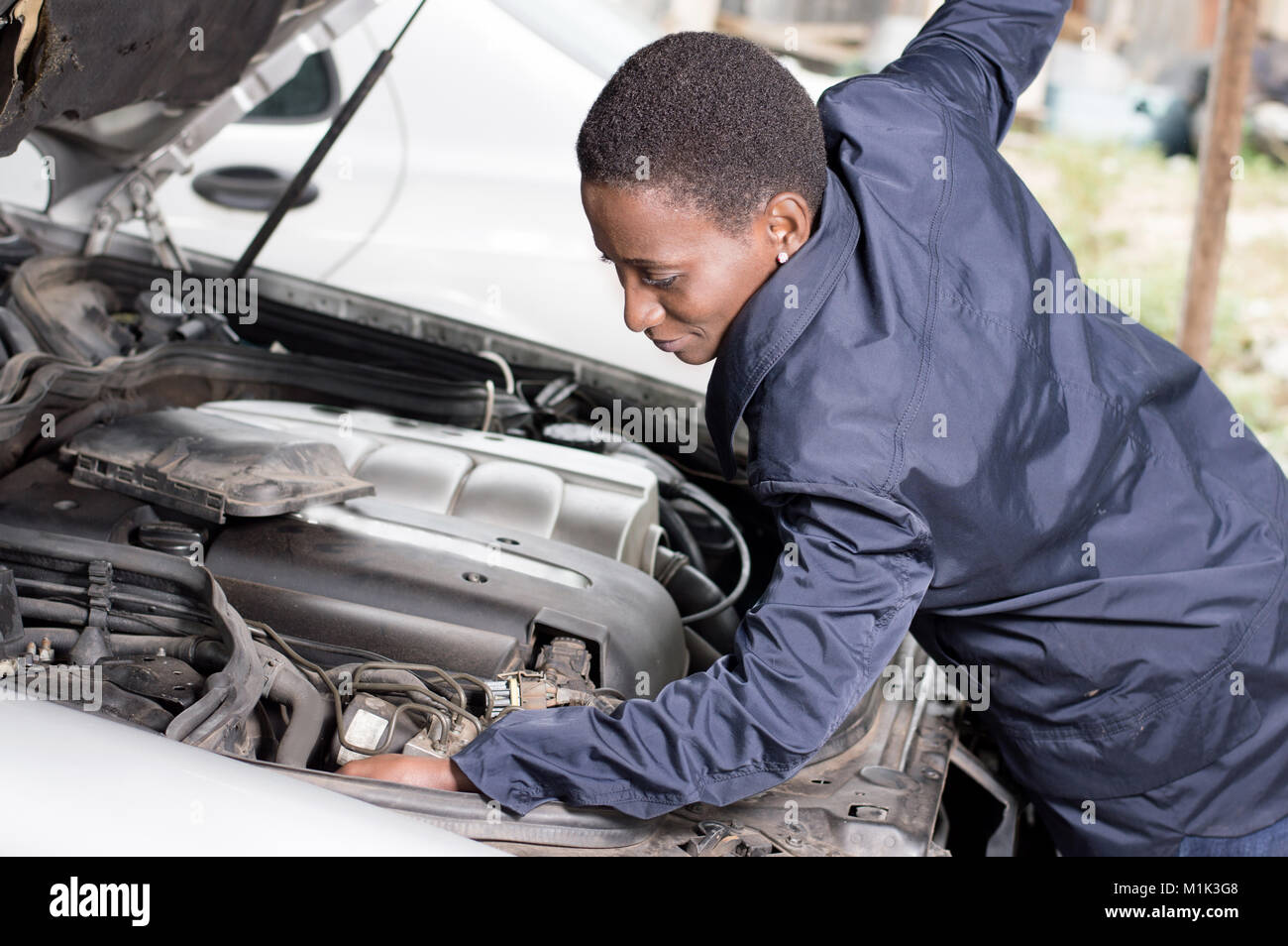 Mechanic repairs the engine of a car in his workshop. - Stock Image