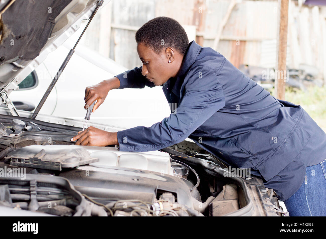 Mechanic  repairs the engine of a car in her  workshop. - Stock Image