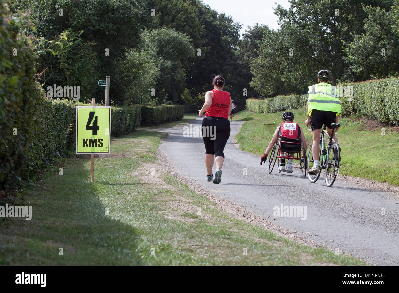 Wheelchair athlete with cycle marshal and woman runner pass 4 km sign - Stock Image