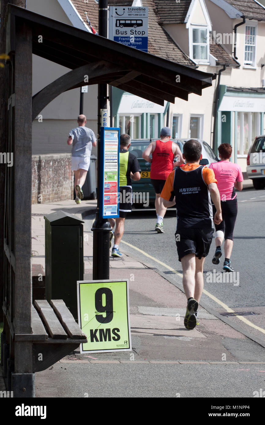 Runners in a 10km road race pass the 9 kilometre marker - Stock Image