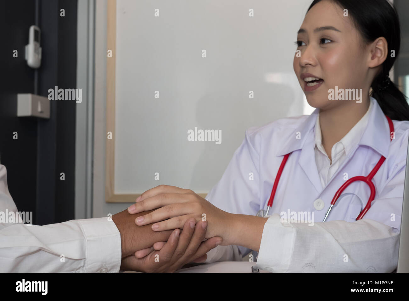 doctor holding patient hand & comforting him for bad news. physician support and encourage a man for medical - Stock Image