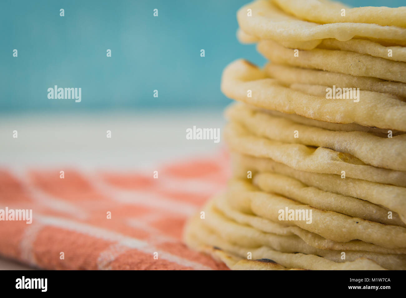 Flour Tortilla Stack with Copy Space to Left over orange napkin - Stock Image
