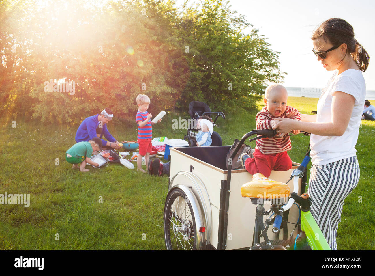 Mother playing with son on bicycle - Stock Image