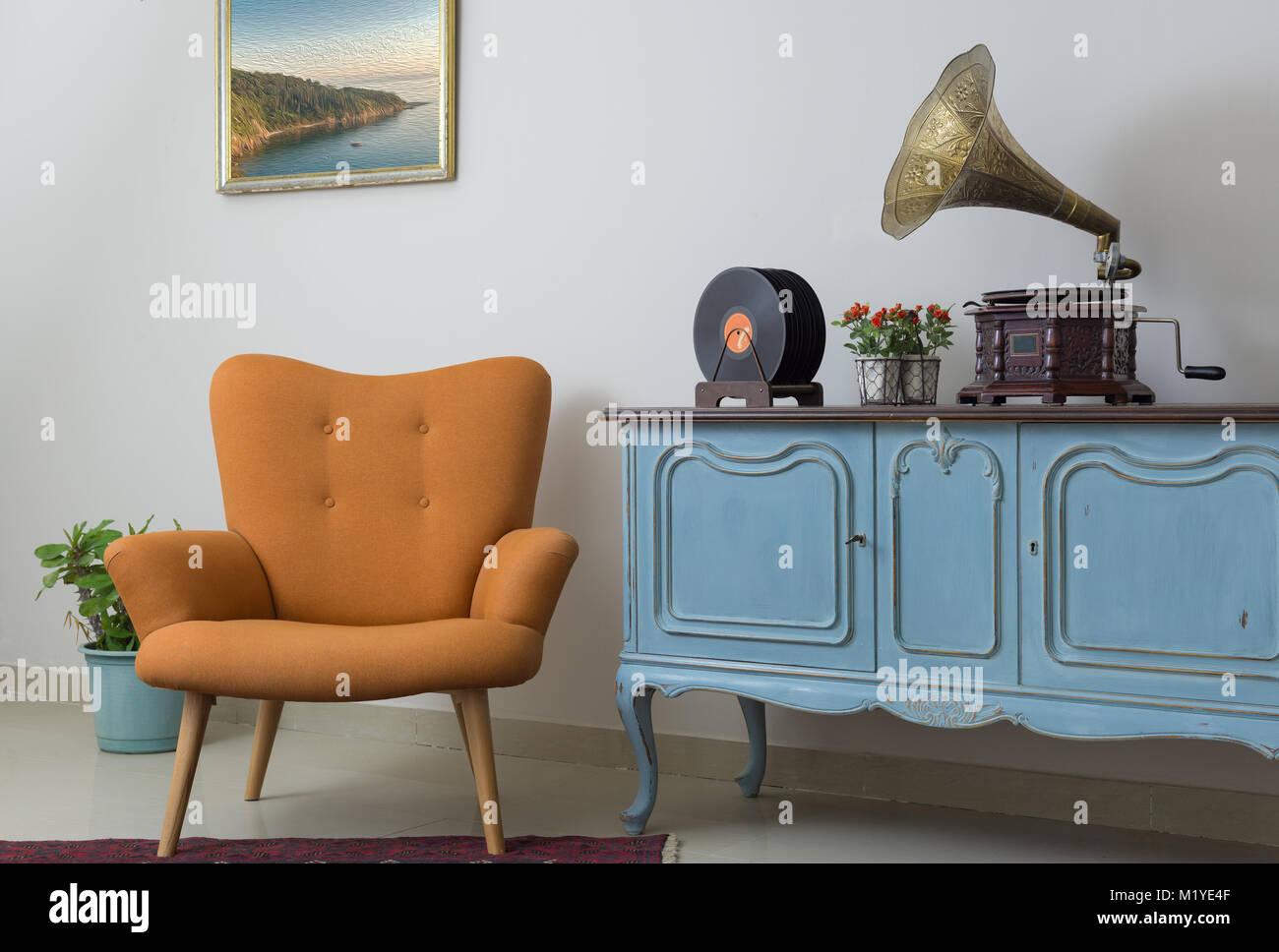 Interior of retro orange armchair, vintage wooden light blue sideboard, old phonograph (gramophone), vinyl records - Stock Image