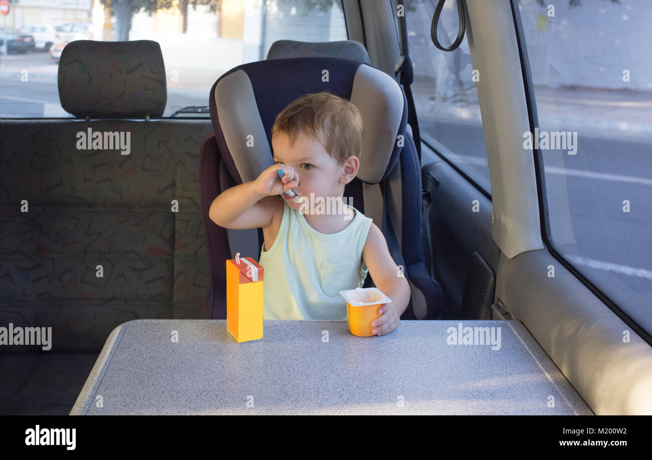 Cute little boy sitting father van and eating yogurt and orange juice. Resting on the way concept - Stock Image