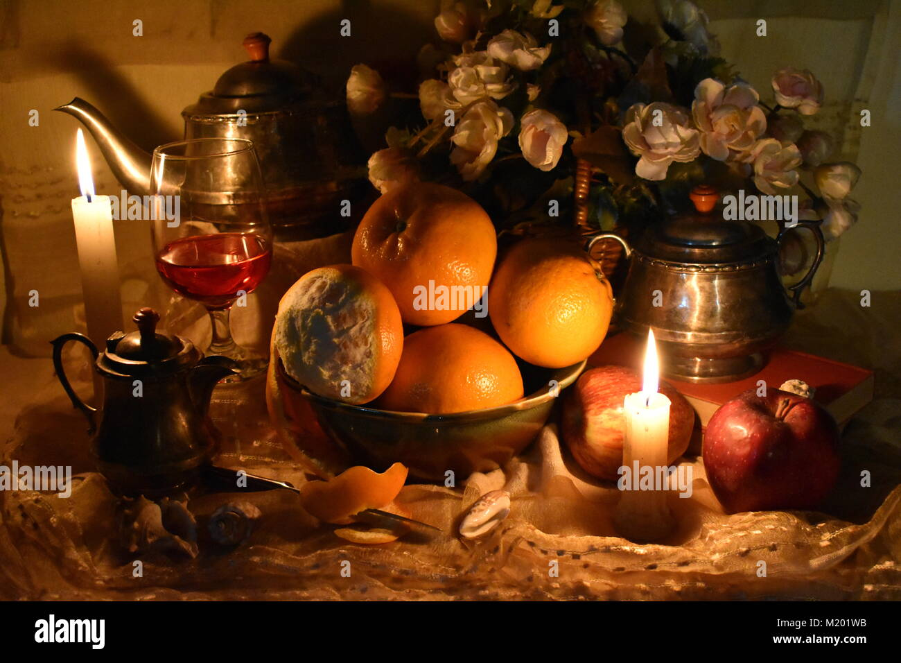 Still life inspired by the Dutch Masters. Classic still life with fruits, orange peel, old tea pot, books, candles, - Stock Image