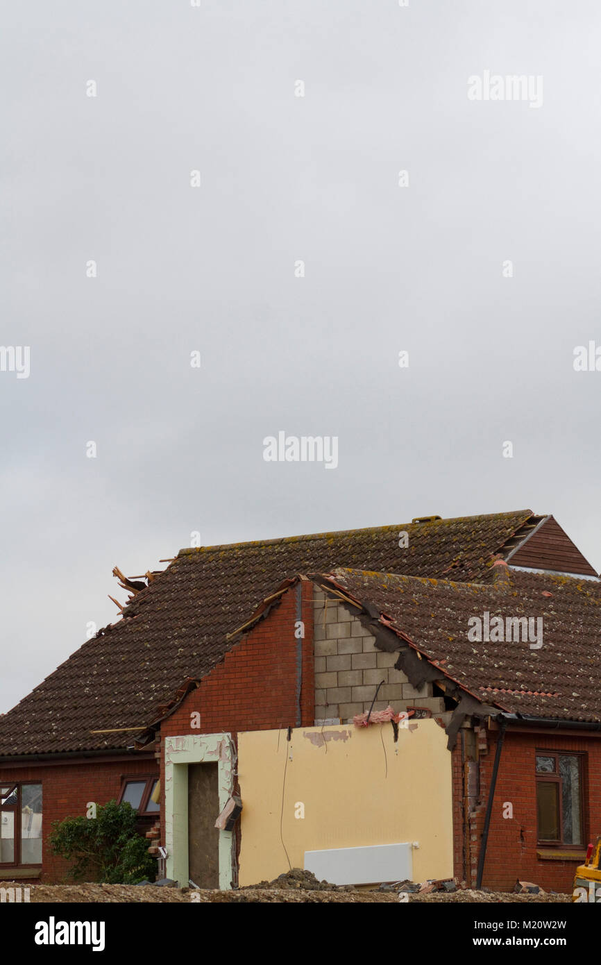 A partly demolished modern building against a dull sky - Stock Image