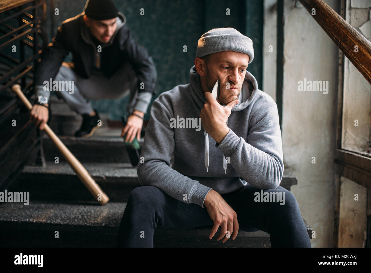 Two male hooligans are sitting on the stairs. Street robbers with baseball bat and knife waiting for victim. Crime - Stock Image