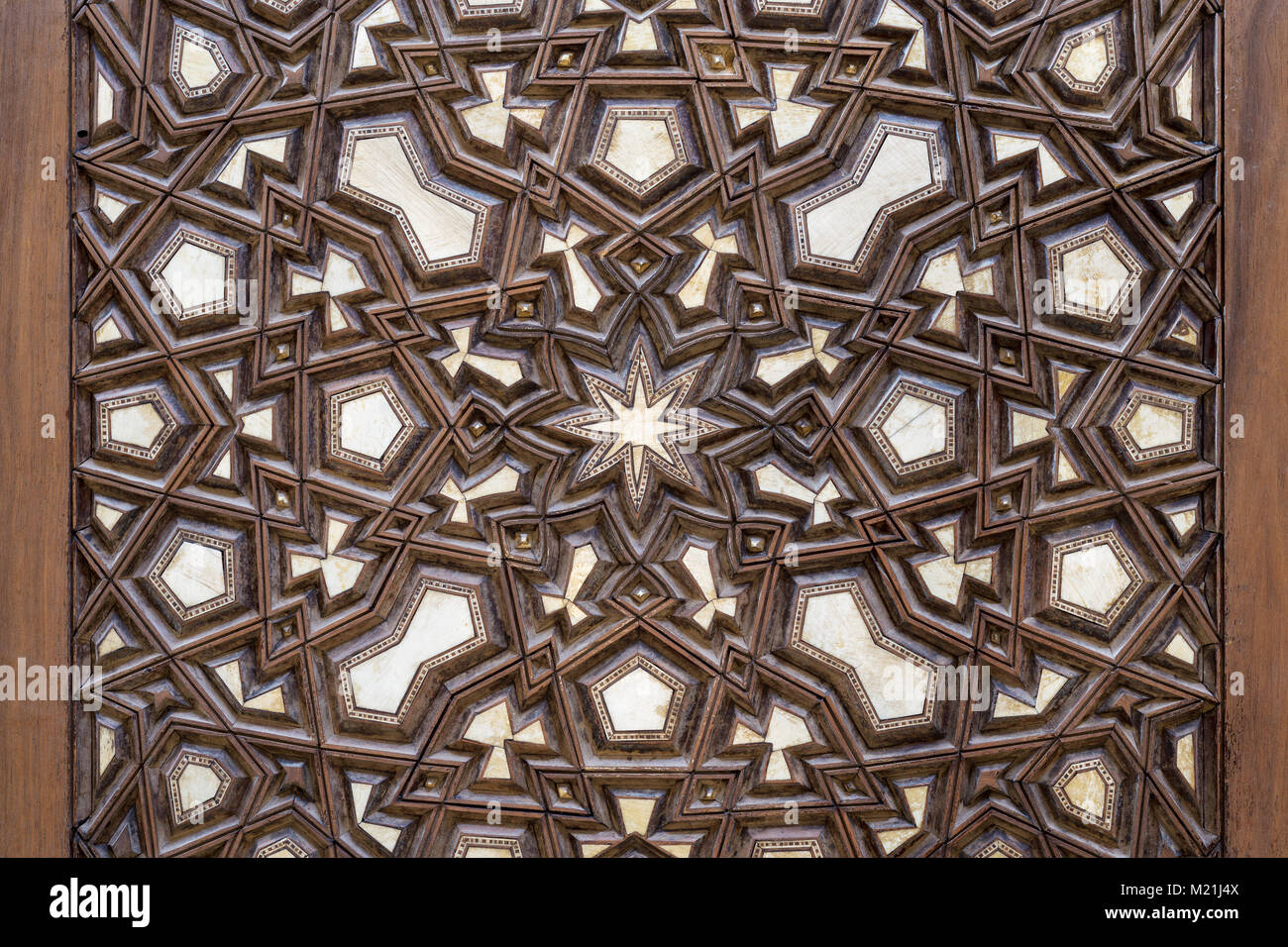 Closeup of arabesque ornaments of an old aged decorated wooden door - Stock Image