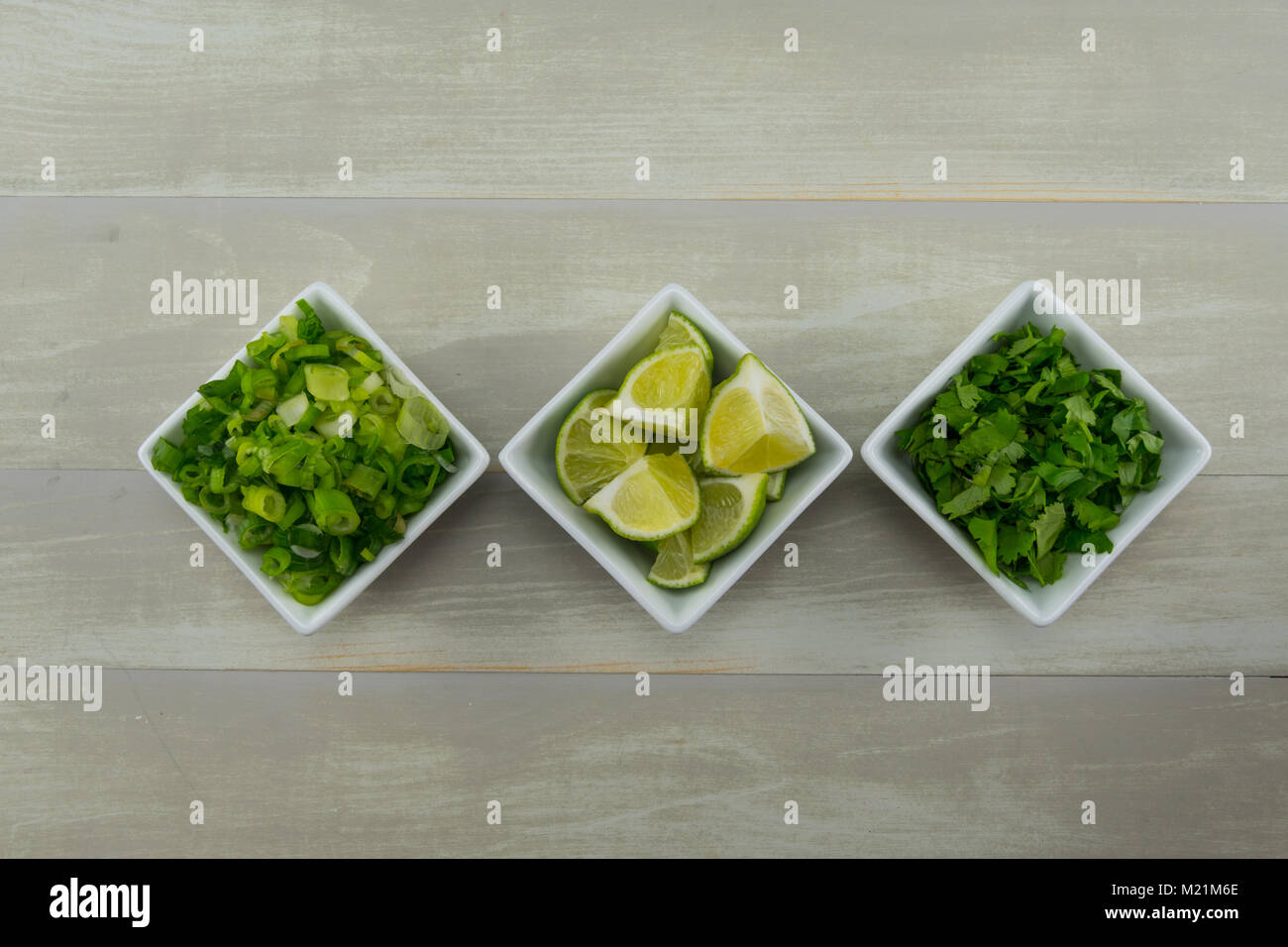 Row of Onion Lime and Cilantro in White Bowls - Stock Image