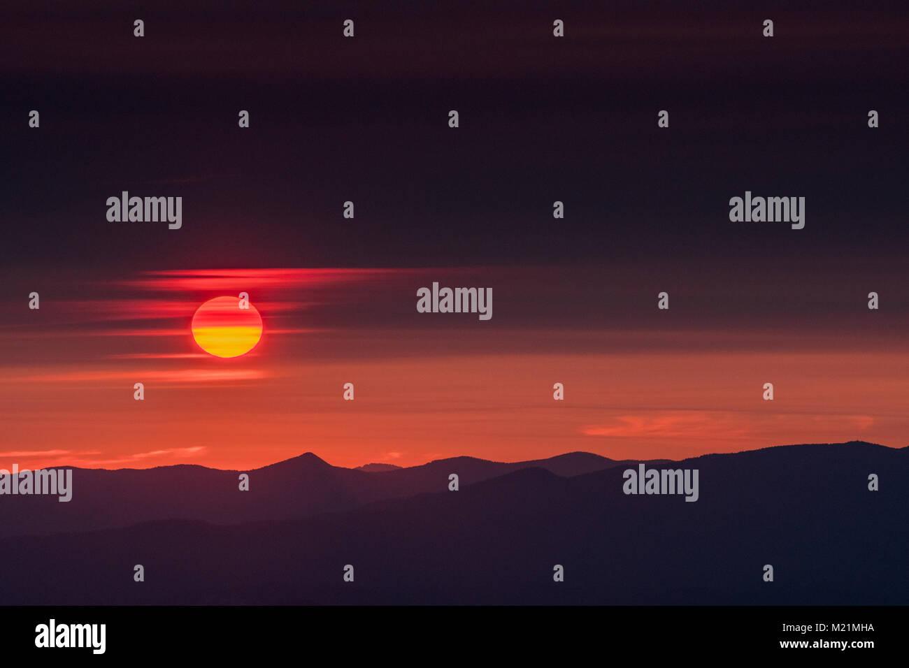 Sun Slips Through Wispy Clouds over mountain range - Stock Image
