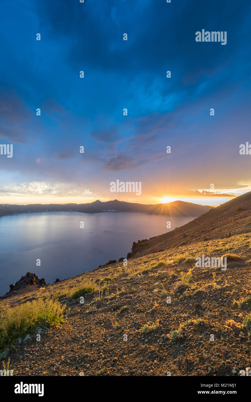 Sunbursts Over The Rim Of Crater Lake in summer afternoon - Stock Image
