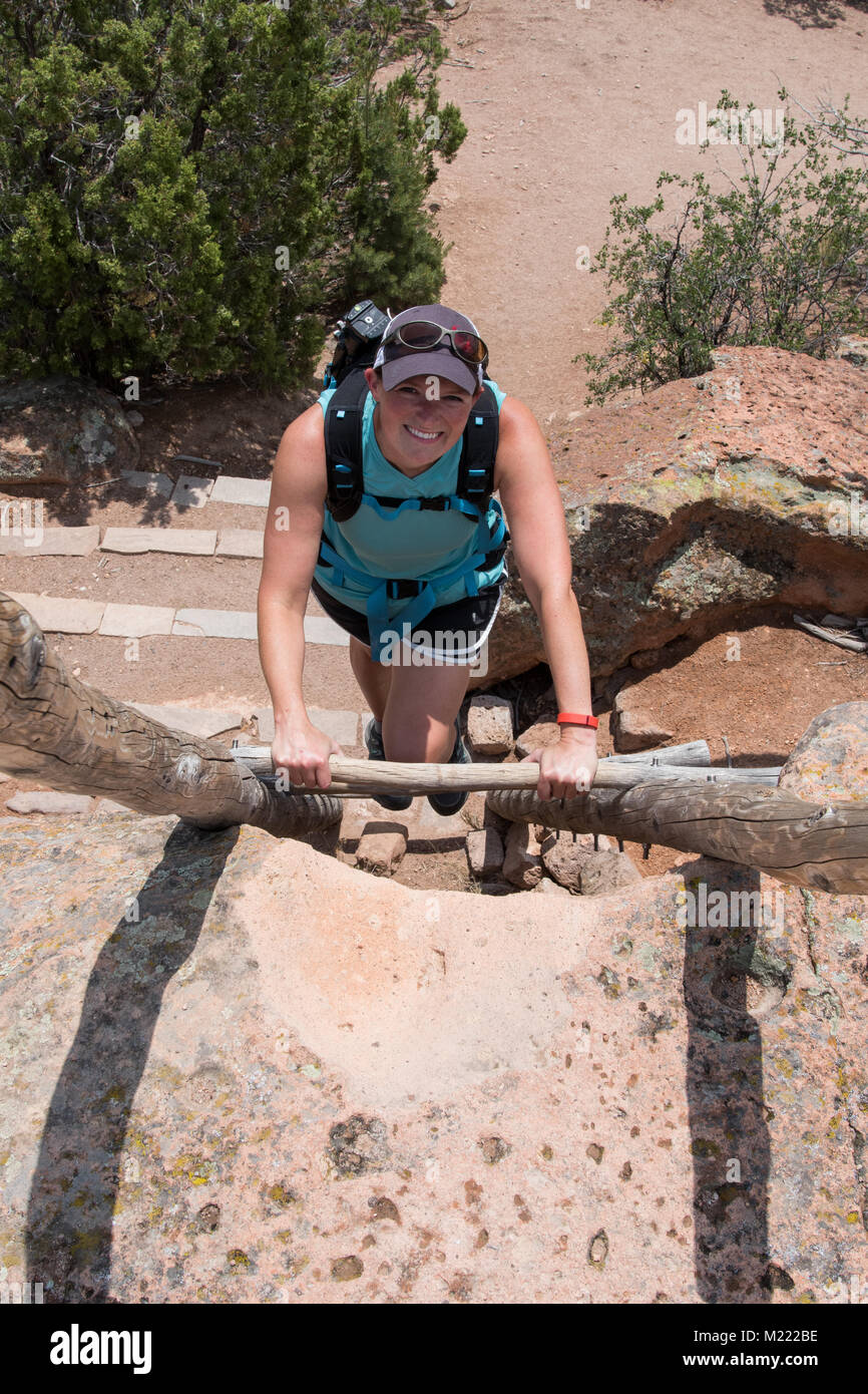Woman Climbing Ladder in Bandelier National Monument - Stock Image