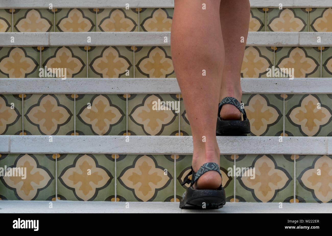 Woman Walks up Patterned Tile Staircase in Sandals - Stock Image
