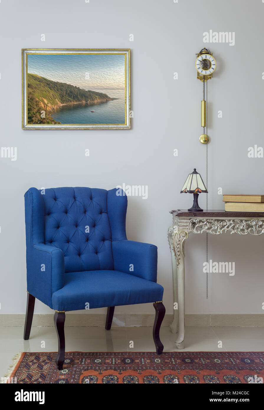 Vintage Furniture - Interior composition of retro blue armchair, vintage wooden beige table, table lamp, books, - Stock Image