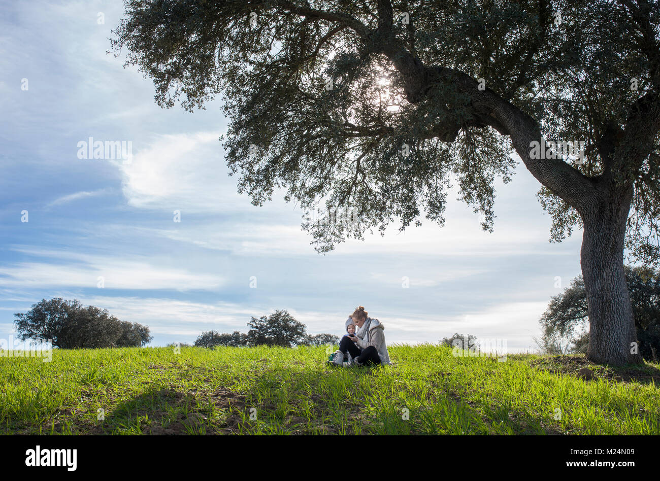 Mother and son playing with mobile at nature. Enjoying nature in family concept - Stock Image