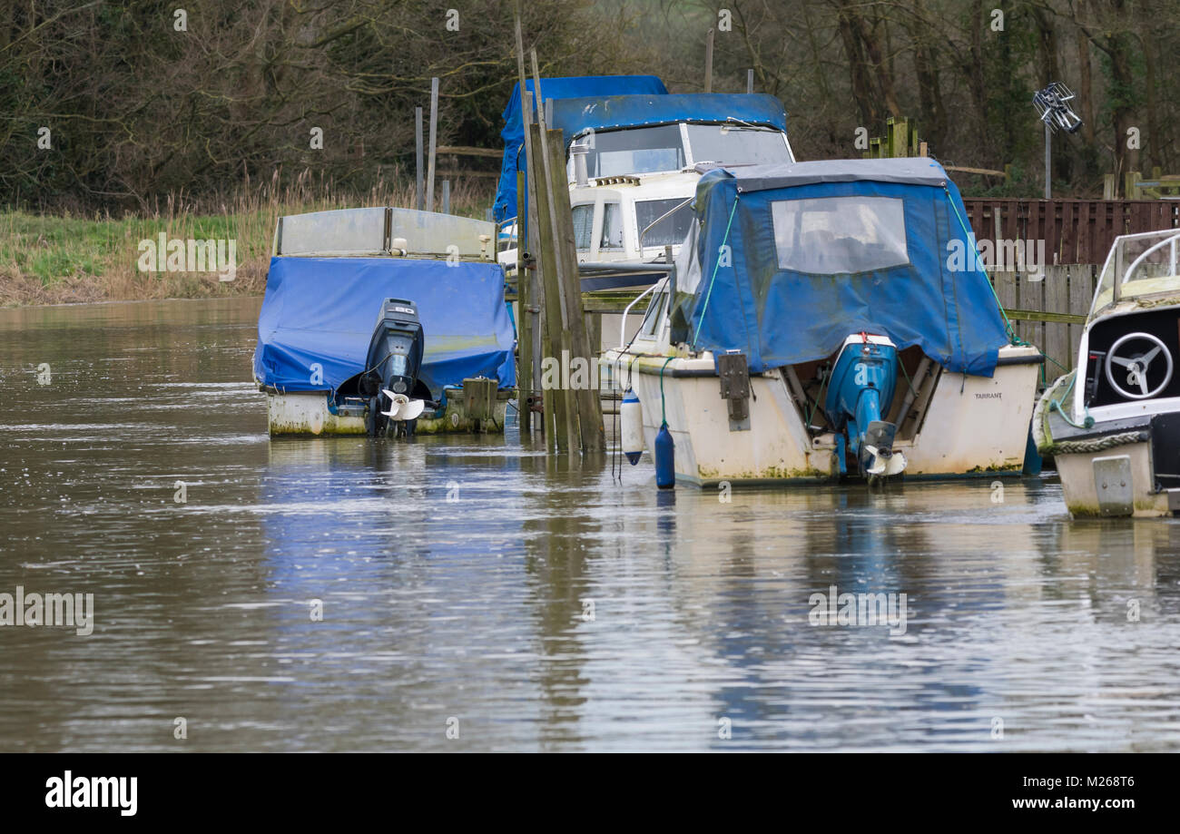 Small pleasure boats moored up and covered for the Winter months in West Sussex, England, UK. - Stock Image