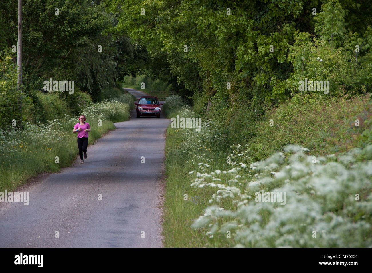 Woman jogger in pink top and country lane with car approaching - Stock Image