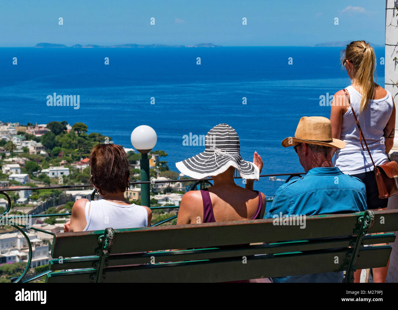 visitors enjoying the view over the bay of naples from the island of capri, italy. - Stock Image