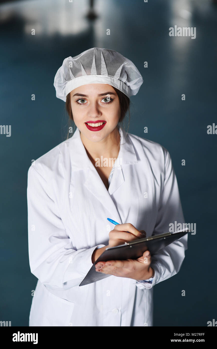 girl scientist or worker in white uniform makes notes on paper against the background of modern factory equipment. - Stock Image