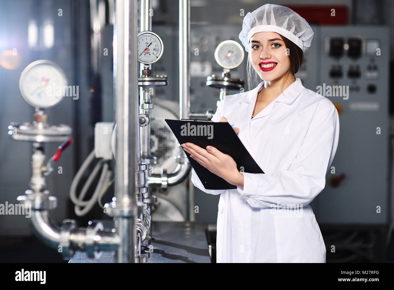 girl is making a note on paper against the background of factory equipment - Stock Image