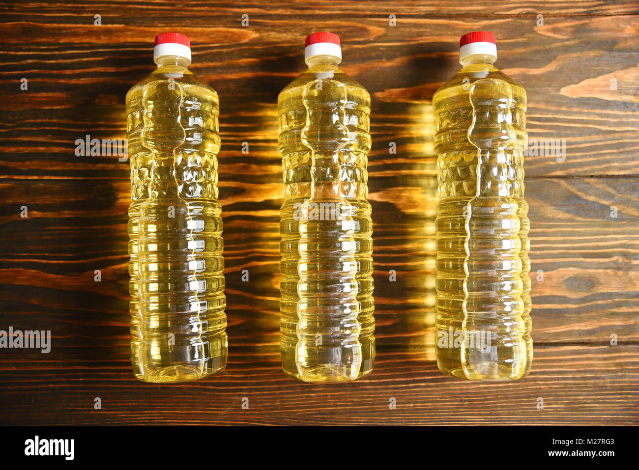 plastic bottles with sunflower oil on a wooden background - Stock Image