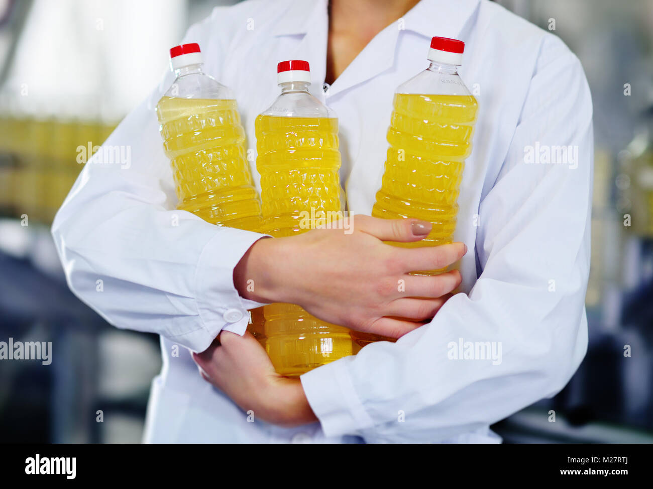 line of food production of refined sunflower oil. Girl worker at a factory on a conveyor background with bottles - Stock Image
