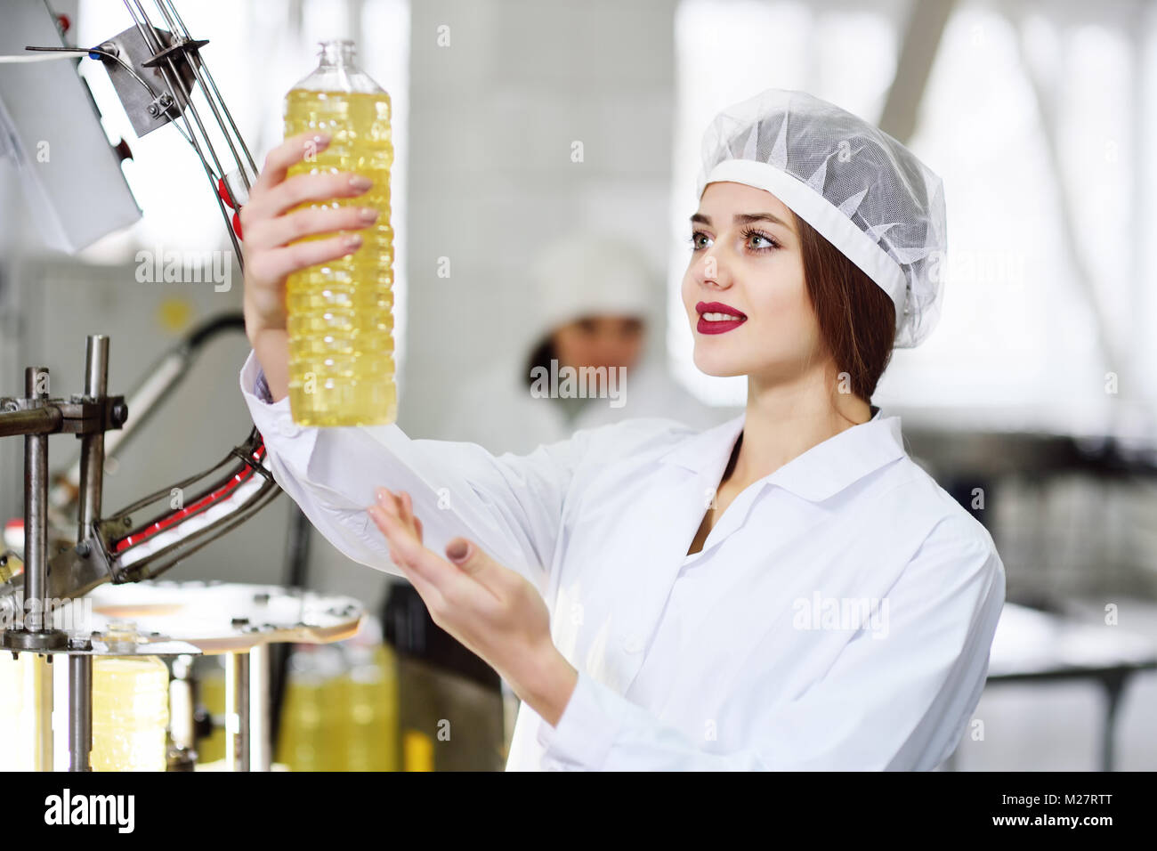 a beautiful young girl in white uniform or a working dressing gown with a bottle of sunflower oil in her hands on - Stock Image