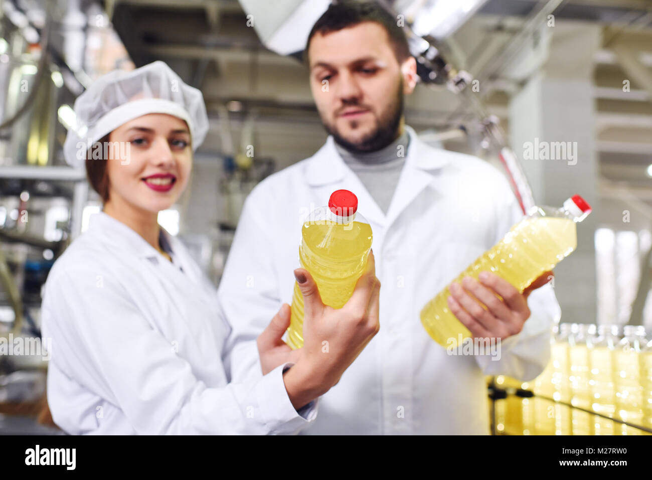 a man and a woman in white overalls with bottles of sunflower oil in their hands on the background of a line of - Stock Image