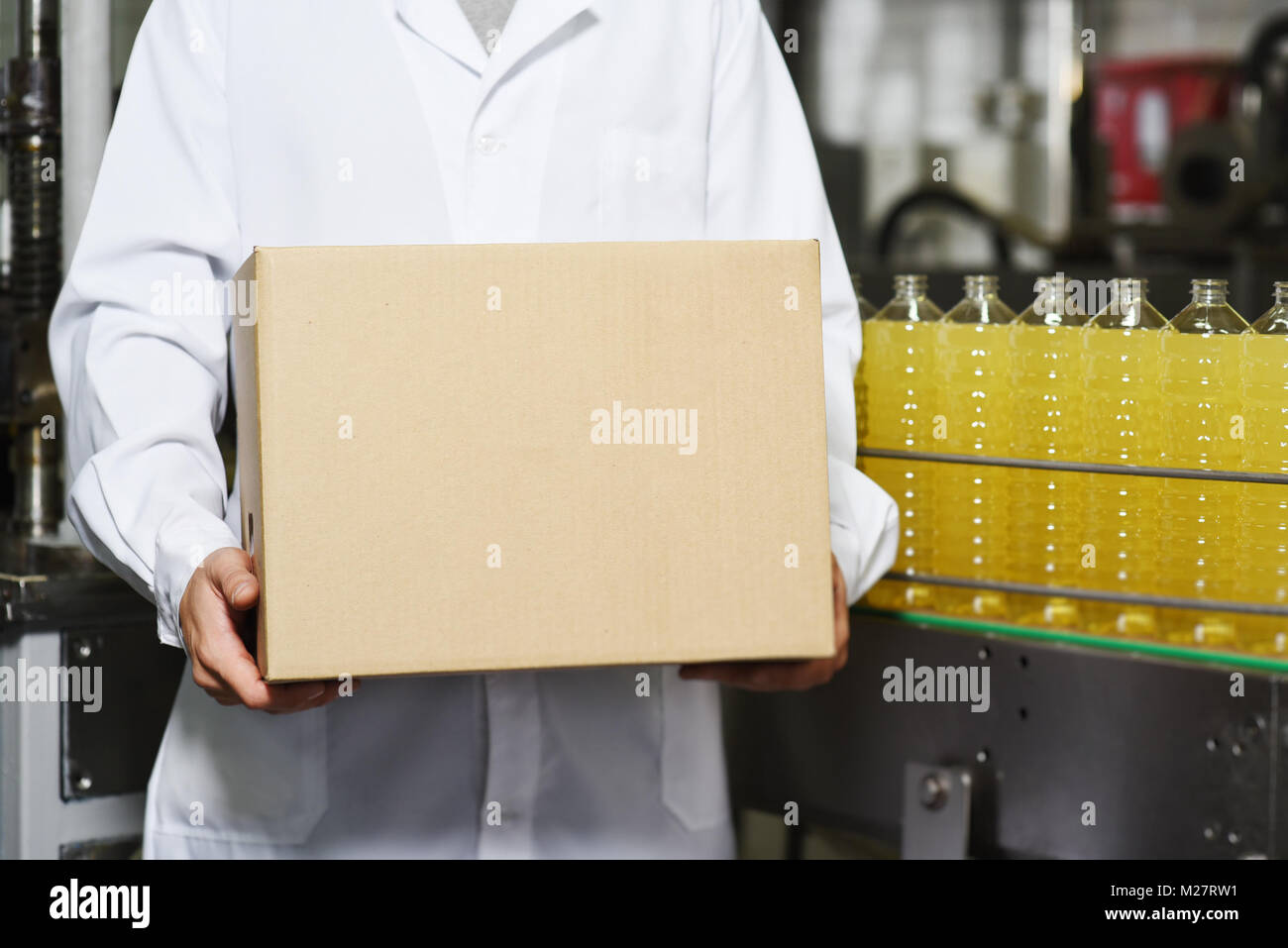 man with a cardboard box on the background of the line for food production of sunflower oil - Stock Image