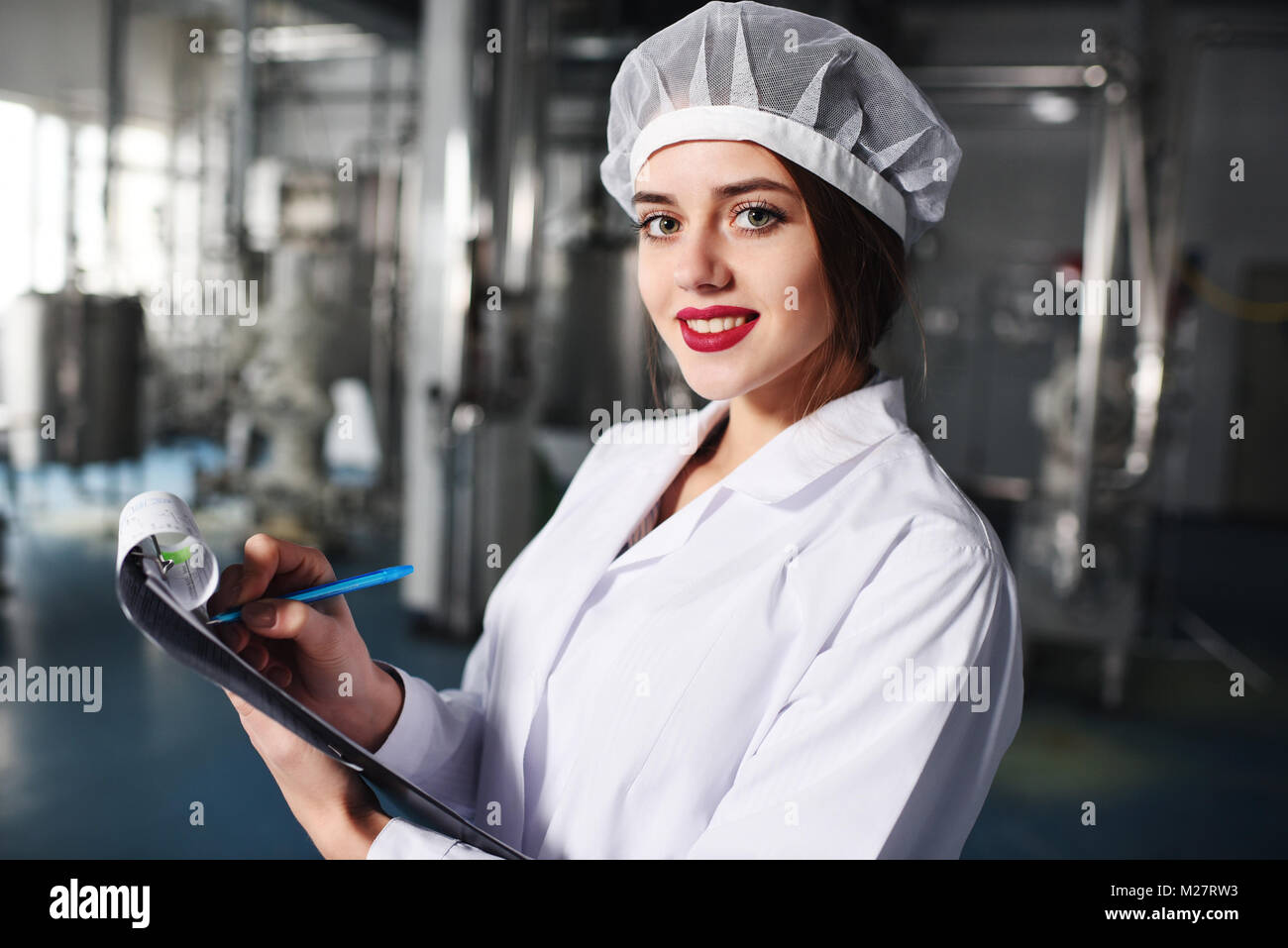 a pretty young girl scientist or worker in white uniform makes notes on paper against the background of modern factory - Stock Image