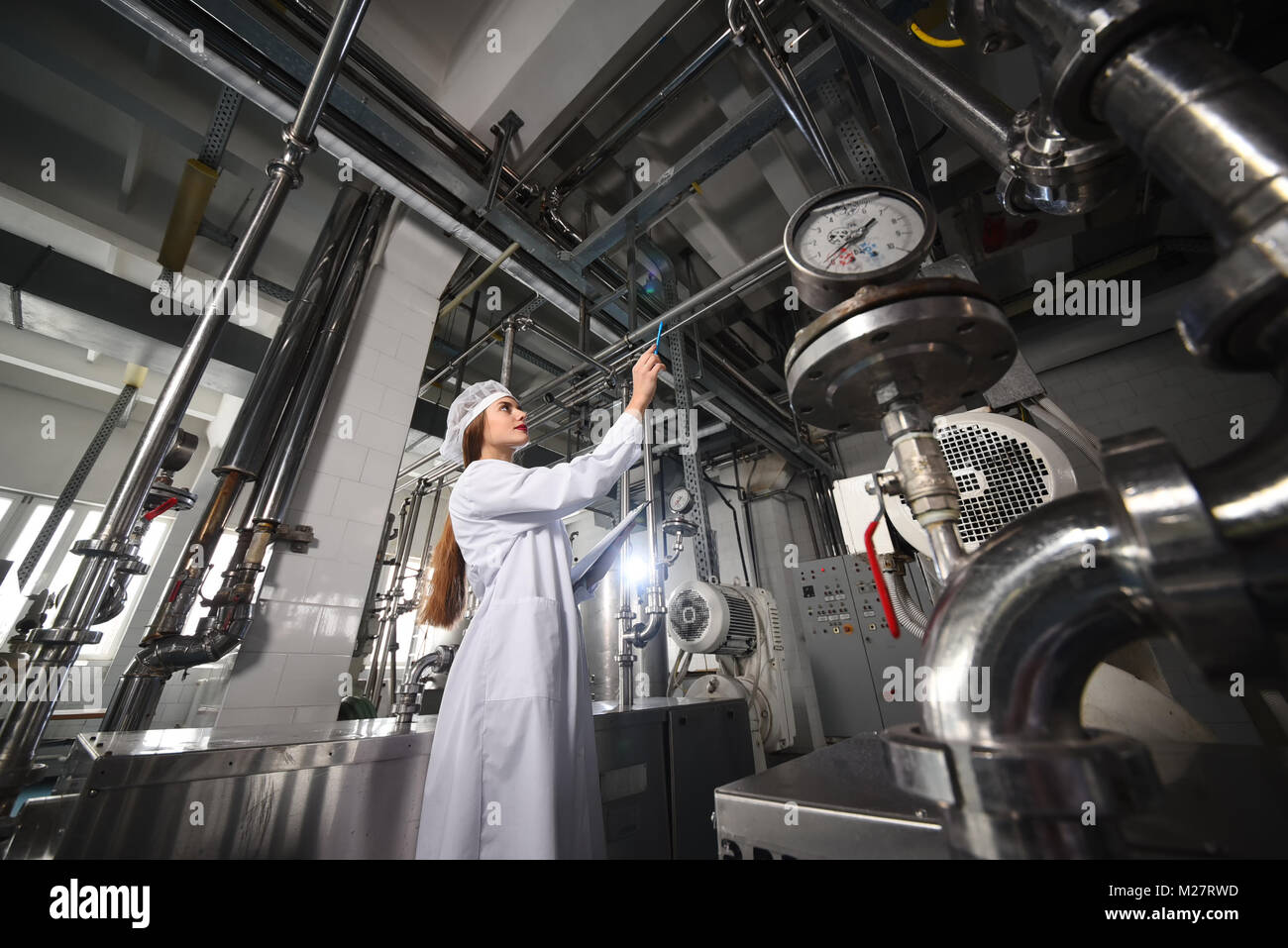 beautiful young girl in white working clothes is making a note on paper against the background of factory equipment - Stock Image