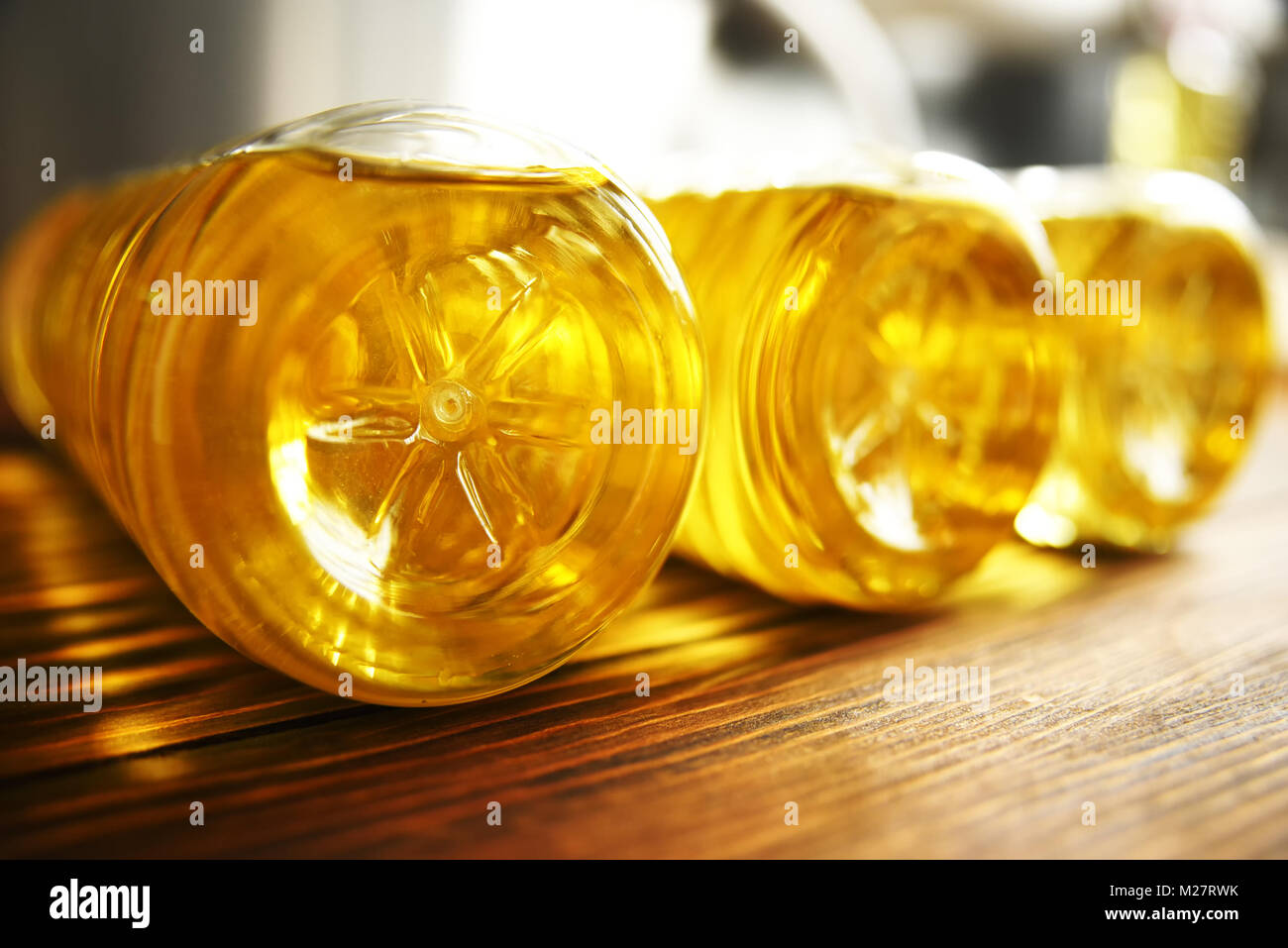 plastic bottles with sunflower oil on a wooden background close-up - Stock Image