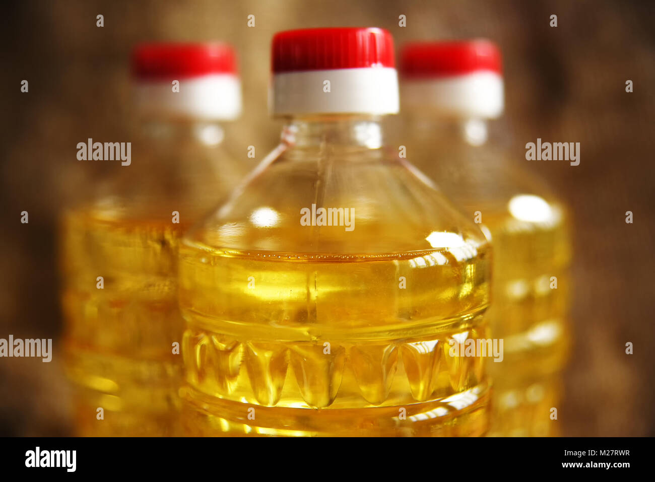 bottles with sunflower oil on a background of burlap closeup - Stock Image
