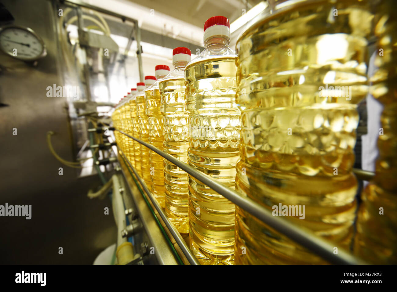 line or conveyor for food production of sunflower oil. Bottles with vegetable oil close-up against the background - Stock Image