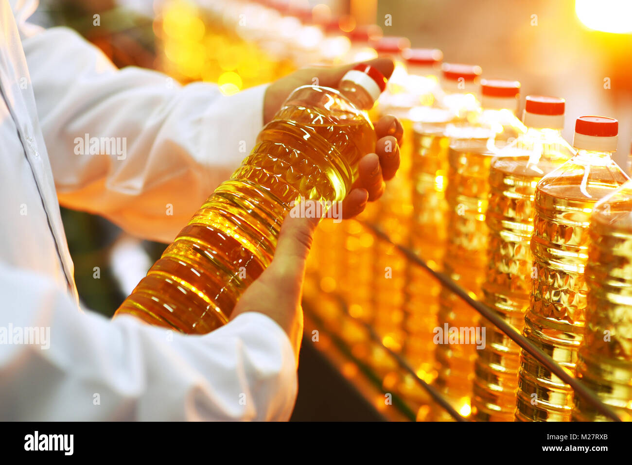Sunflower oil production plant. Bottling line of vegetable oil in bottles - Stock Image