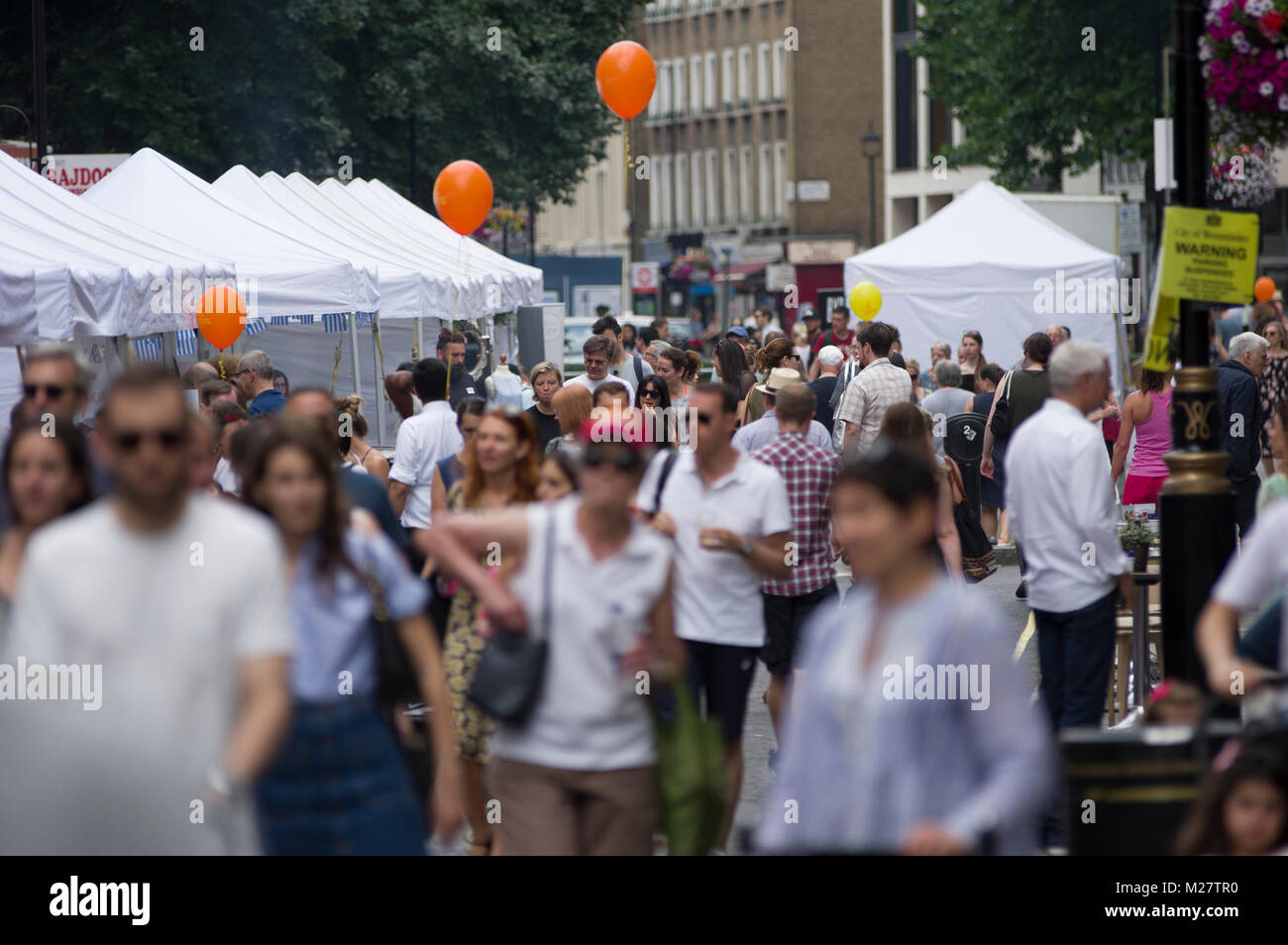 Crowd scene at the Marlyebone Summer Fayre Marlyebone Food Festival in London on a sunny day with yellow balloons - Stock Image