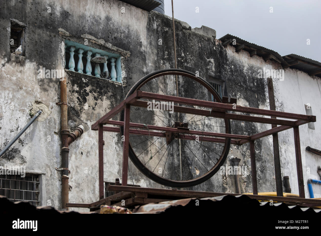 old bicycle wheel mounted on a rusty steel structure of unknown use, perhaps a knife sharpener - Stock Image