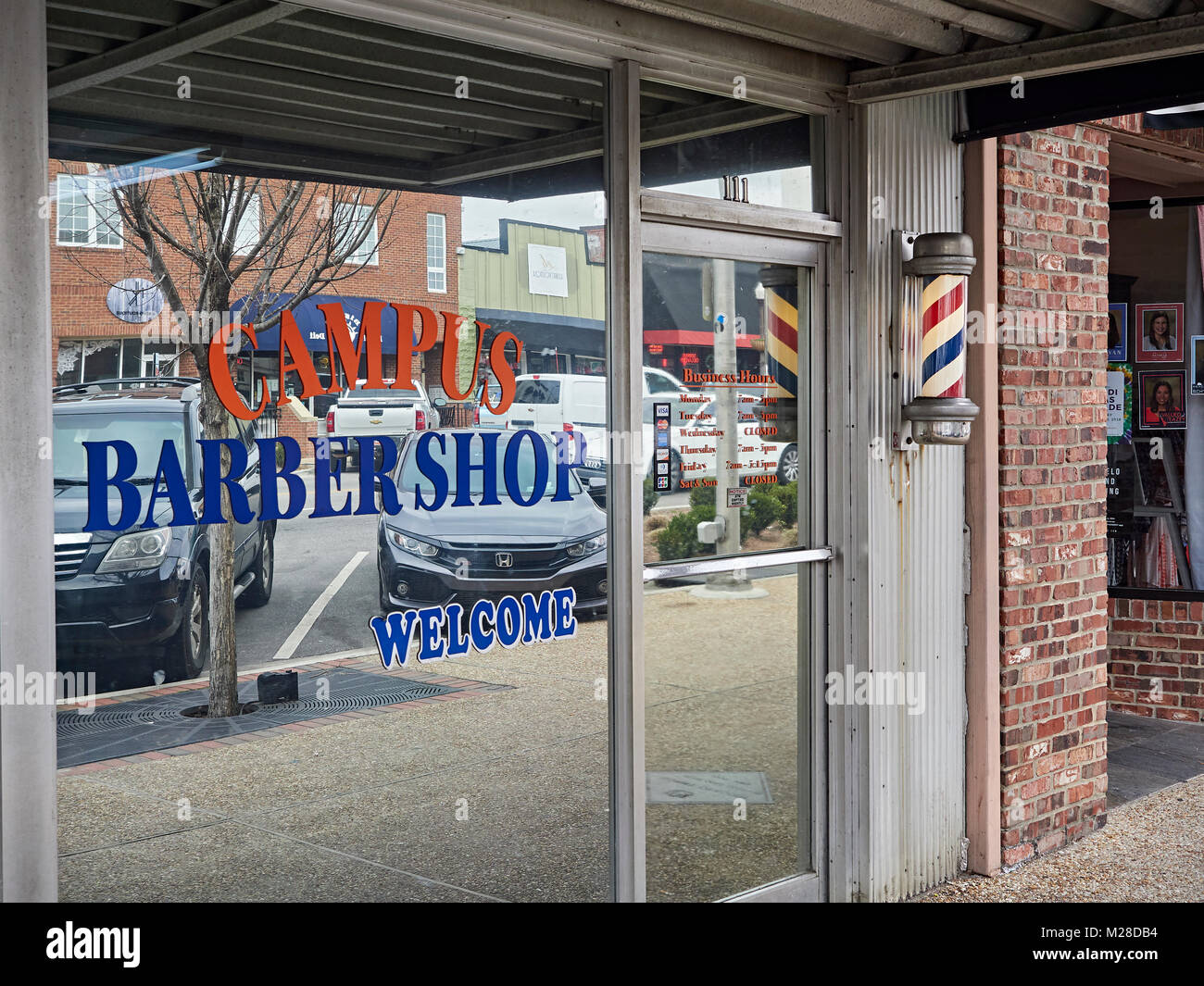 Front exterior entrance of the Campus Barber Shop business with lighted barber pole in Auburn Alabama, USA. - Stock Image