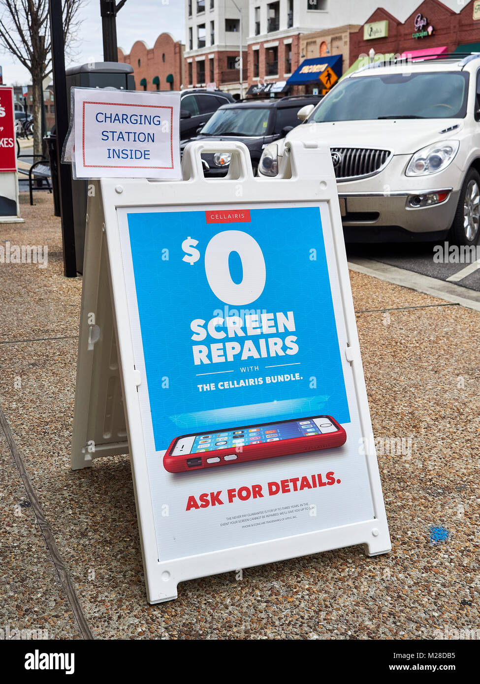 Sidewalk sign advertising free cell phone screen repairs with Cellariris bundles and indicating a charging station - Stock Image