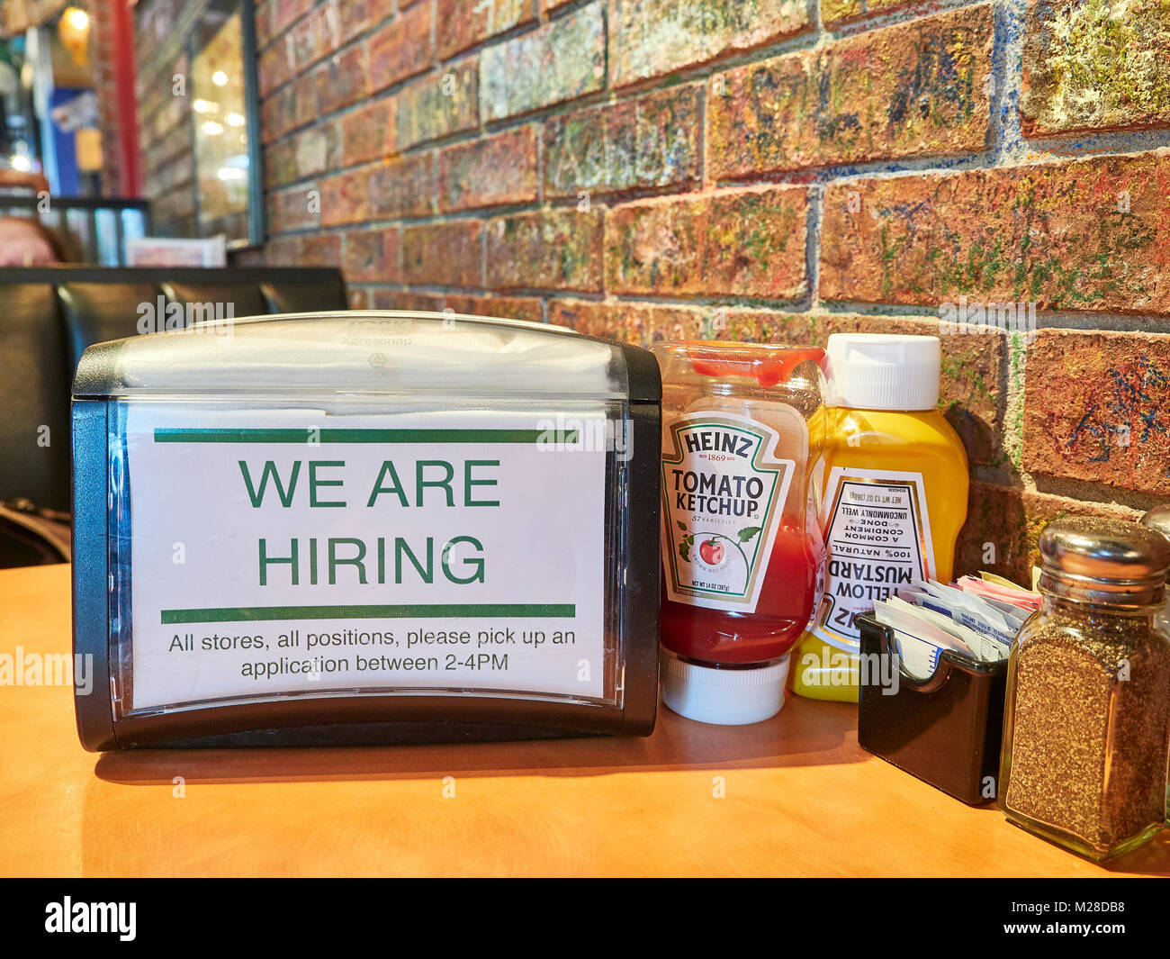 Inside or interior of restaurant table and napkin holder with we are hiring or a help wanted sign in Niffer's - Stock Image