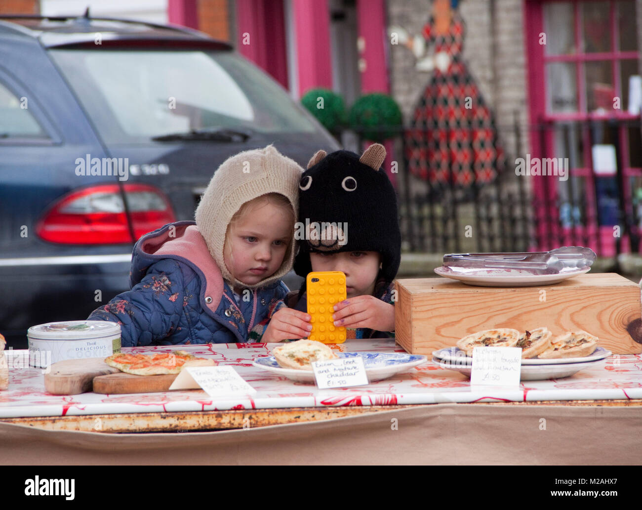 Two children in knitted balaclavas on a food stall messing with a bright yellow mobile phone - Stock Image