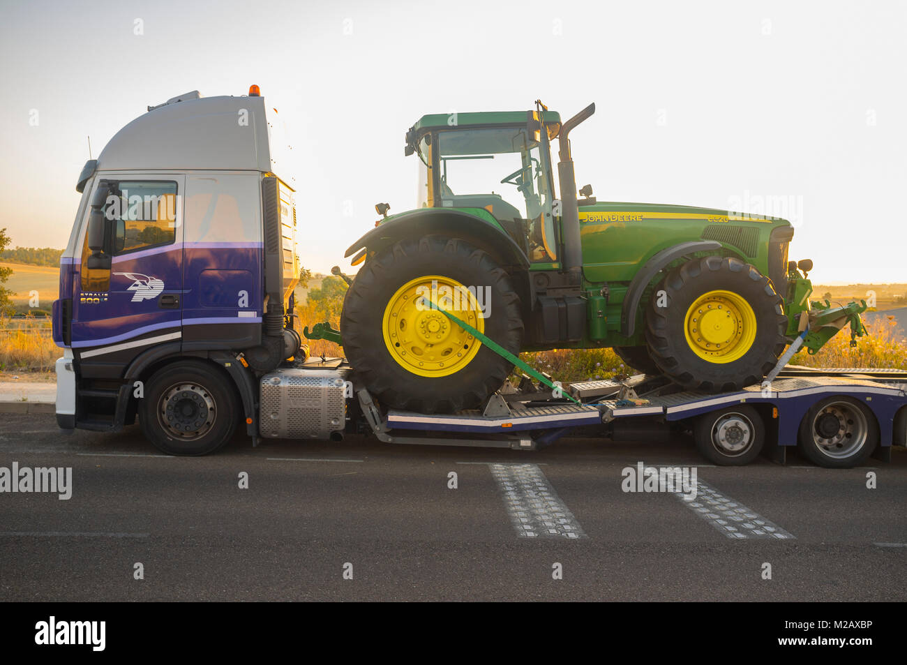Badajoz, Spain - August 6th, 2017: Auto-transport trailer carrying the Row Crop Tractor John Deere 8320 - Stock Image
