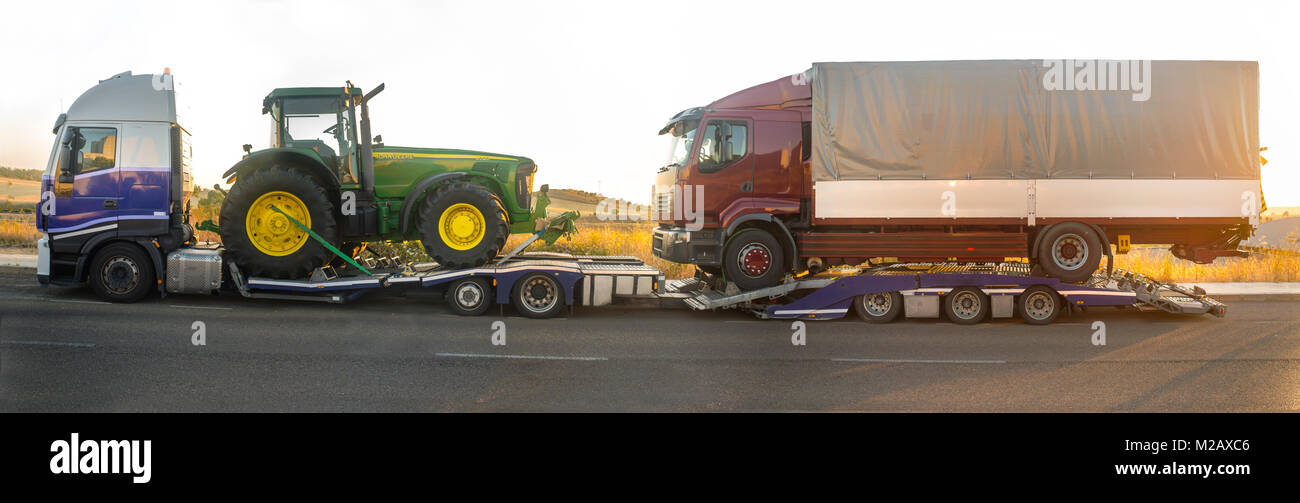 Badajoz, Spain - August 6th, 2017: Iveco Stralis E5 Heavy-duty truck with an auto-transport trailer carrying tractor - Stock Image