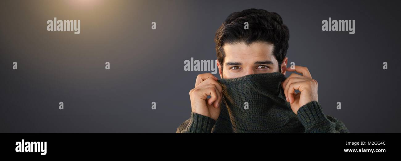 Man hiding under jumper with eyes peering out - Stock Image