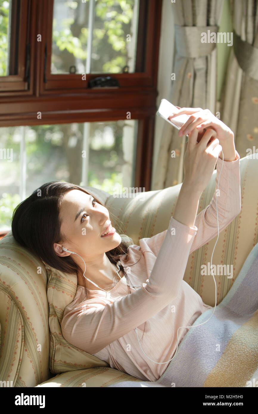 Young women watch mobile phones - Stock Image