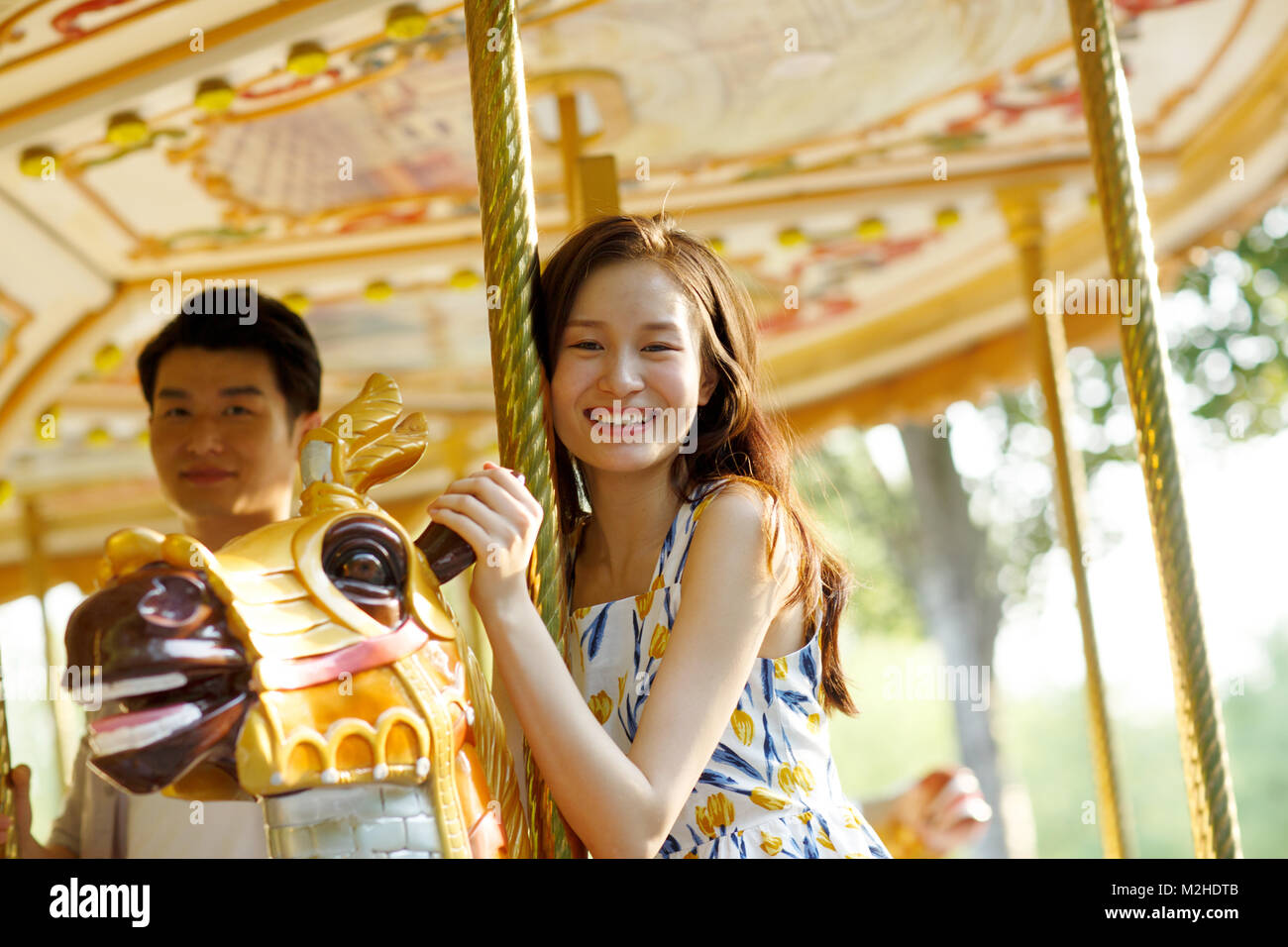 Young lovers riding merry rides on the playground - Stock Image