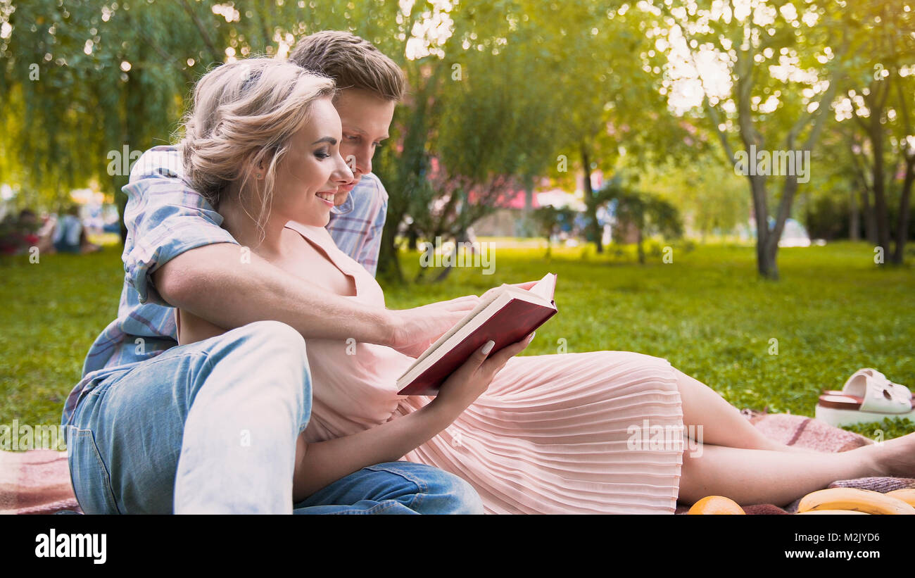 Caring guy reading story to his beautiful lady, gently hugging her, date in park - Stock Image