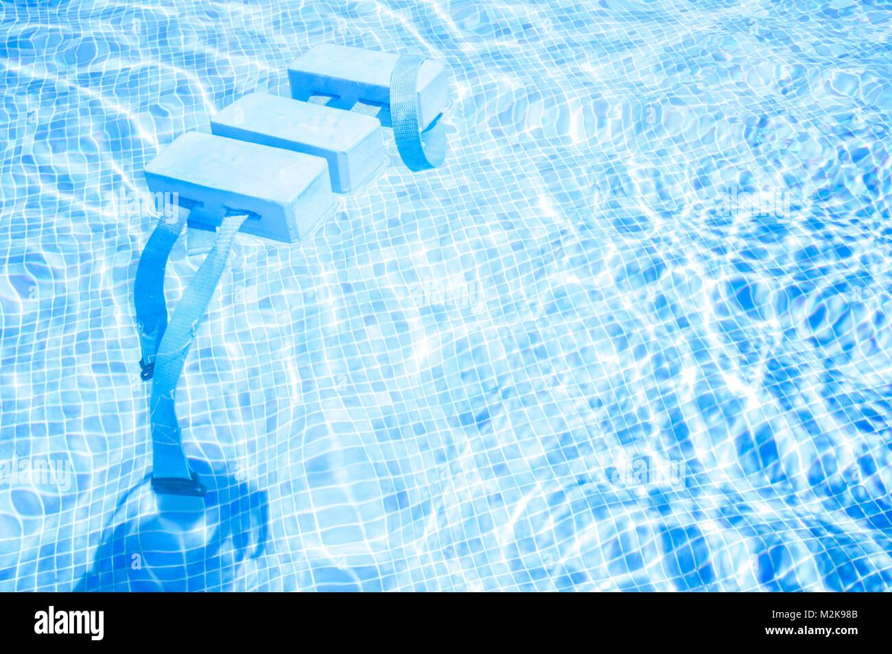 Swimming Float Belt for Kids Swim Training on swimming pool surface. Swiming pool bottom made of gresite - Stock Image